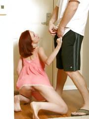 Red haired teen beauty in pink skirt kneels on the floor sucking cock