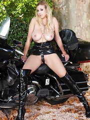 Blonde babe Sapphire soloing in latex on motorbike outdoors